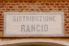 Old sign ration-distribution written in  italian language. Sign made of cement indicating the writing ration-distribution  on a bricks wall Royalty Free Stock Photos