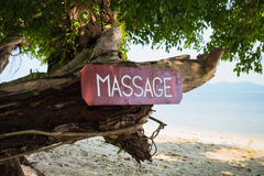 Old signboard with the inscription, massage, on a tropical beach Royalty Free Stock Photo
