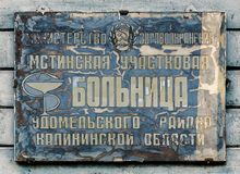 Old signboard rural hospitals. The old cracked discolored sign rural hospitals. Inscription in Cyrillic Stock Photo