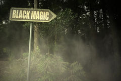 Old signboard with text black magic near the sinister forest Stock Image