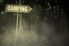 Old signboard with text camping near the sinister forest. Vintage old signboard with text camping near the sinister forest royalty free stock image