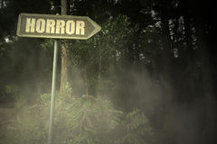 Old signboard with text horror near the sinister forest Royalty Free Stock Images