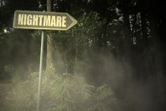 Old signboard with text nightmare near the sinister forest Royalty Free Stock Photo