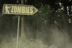 Old signboard with text zombies near the sinister forest. Vintage old signboard with text zombies near the sinister forest stock photography