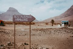 Old signpost in abandoned barren desert scenery. Volcano rugged on the horizon. Sao Vicente Cape Verde. Old signpost in abandoned barren scenery. Volcano rugged Royalty Free Stock Image