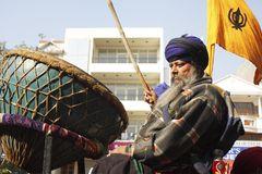 An old sikh gentleman beating a huge drum Nagara. An old sikh gentleman with flag while beating a huge drum called nagara on a street in new delhi, india stock images