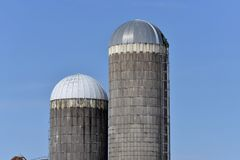 2 old silos in southern wisconsin. One painted cap and one unpainted cap stock image