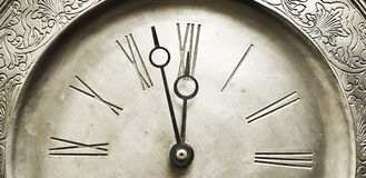 Old silver clock with roman numbers indicating it's about time. Royalty Free Stock Photography