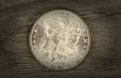 Old Silver Dollar. Vintage concept of a Silver Dollar in very good condition on aged wood. Slight vignette border around coin Stock Photography