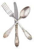 Old silver knife fork and spoon crossed isolated Stock Images