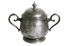 An old silver metal sugar bowl with a lid and ornament. Metal punctles with scratches and patina. Stock Images