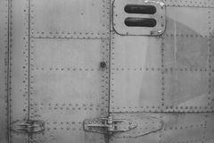 Old silver metal surface of the aircraft fuselage with rivets. Fuselage detail view. Airplane metallic fuselage detail. With rivets royalty free stock photography