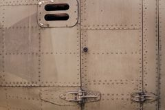 Old silver metal surface of the aircraft fuselage with rivets. Fuselage detail view. Airplane metallic fuselage detail Royalty Free Stock Images