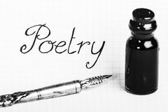 Old pen and ink bottle for poetry. An old silver pen and a small bottle of ink are on a sheet of paper where is the write Poetry stock photos