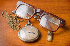 Old silver pocket watch and glasses Royalty Free Stock Photos
