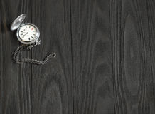 Old silver pocket watch lying on a wooden table. Stock Photography