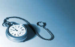 Old silver pocket watches on a chain; on a white background. Focused on dial; picture tinted blue stock images