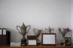 Old silver trophies,. Picture frames and file folders on a sideboard cabinet in an retro style office Stock Image