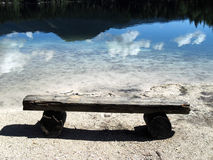 Old simple bench on the shore of mountain lake Stock Images