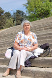 Old,simple lady,2. An old lady sitting down on stone stairs,sunny day Royalty Free Stock Image