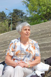 Old,simple lady. An old,simple,lady,sitting on the stone stairs,day light,close up Royalty Free Stock Photography