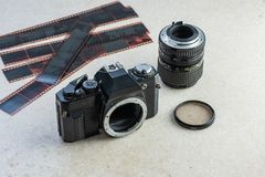 Old single lens reflect camera, lens, filter and films. On white marble table royalty free stock photography