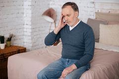 Old sitting man with headache Royalty Free Stock Images