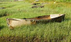 Old skiff. An old discarded fiberglass skiff on a grass covered banking Stock Photography