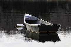 Old skiff moored. Old skiff bobbing at mooring on calm afternoon Stock Photos