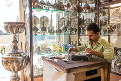 An old skilled artisan makes traditional metal souvenirs in a small workshop. Royalty Free Stock Images