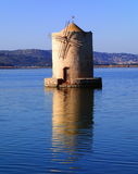Old slanted windmill in water, Orbetello, Italy Stock Images