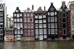 Old slanting canal buildings in Amsterdam. Panorama of a line of narrow old buildings in Amsterdam, Netherlands. The buildings are slanting and wedged together Stock Photo