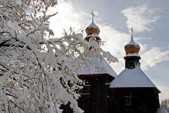 Old Slavic Christian Orthodox church in the snow, with two domes. And crosses on them Royalty Free Stock Photo