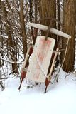 Old sled leans against a tree after a snowfall Royalty Free Stock Images