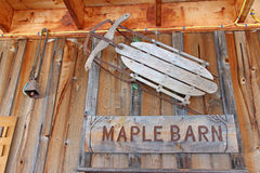 Old sled on wall as decoration with maple barn sign Royalty Free Stock Images