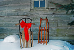 old sleds with red bow  Royalty Free Stock Photos