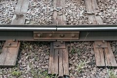 Old sleepers, in city there is a tram line. In nature, a wet wooden board. Coupling of metal rails. Royalty Free Stock Images