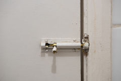 Old slide lock on dirty door Stock Photography