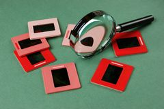 Old slides and a magnifying glass on green. Table stock photo
