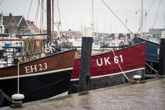 Old smacks in the harbor of Urk on a misty and rainy winter day stock images