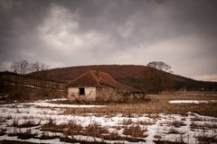 Old small abandoned house on meadow royalty free stock photo