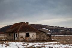 Old small abandoned house on meadow royalty free stock image