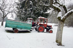 Old small agriculture tractor in winter farm garden. On snow Stock Images