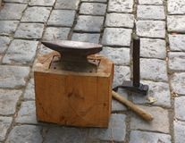 Old small anvil at wooden base with hammers Royalty Free Stock Image