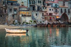 Old small boat in the harbor of Cefalu Stock Photo
