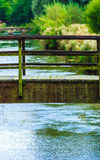 Old small bridge over river in green garden. Royalty Free Stock Images