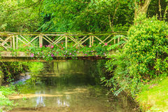 Old small bridge over river in green garden. Stock Photo