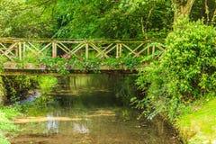 Old small bridge over river in green garden. Royalty Free Stock Photos