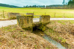 Old small bridge with a rural path and green meadow behind and a Stock Photography