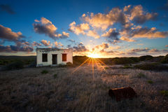 Old small deserted house in field with cloud sunset landscape Royalty Free Stock Image